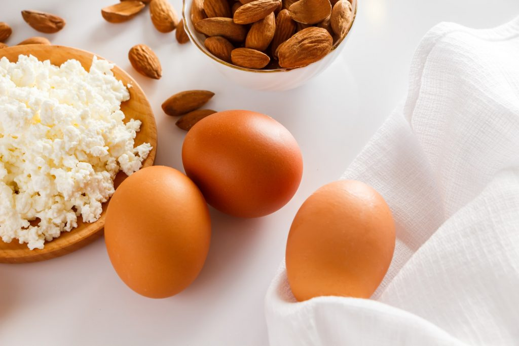 Protein food on a white background - cottage cheese, eggs, nuts