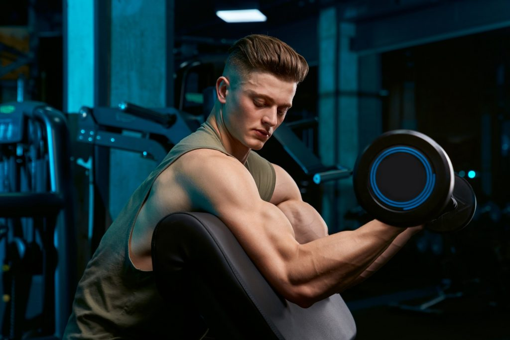 Sportsman building biceps with barbell