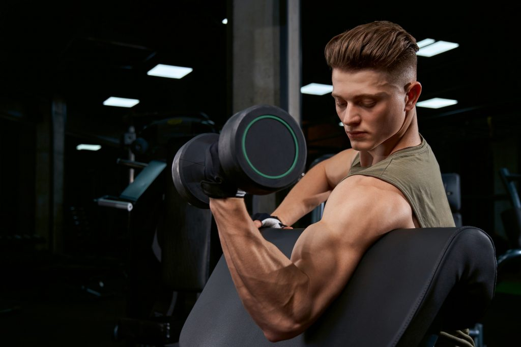 Sportsman training biceps with dumbbell