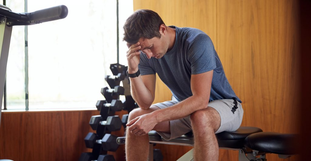 Man Anxious About Body Image Sitting On Weight Bench In Home Gym