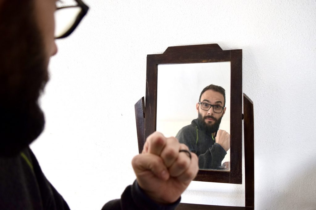 Millennial man looking at the mirror and cheering him up. Narcissistic personality. Empowerment.