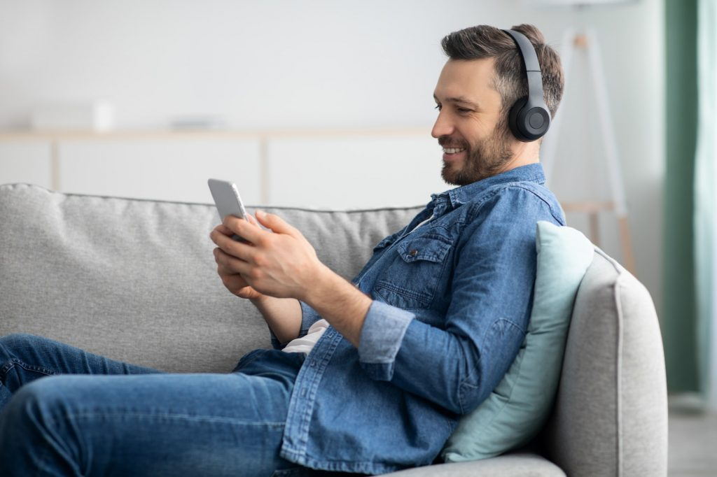 Positive bearded man with headset and mobile phone