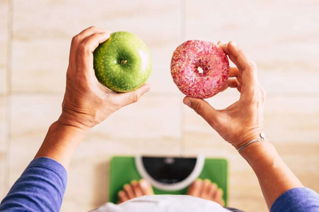 woman on a weight scale with an apple in her left hand and a donut in her right hand