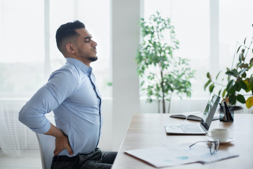 Young Arab businessman having acute back pain, massaging aching muscles, sitting at desk in modern