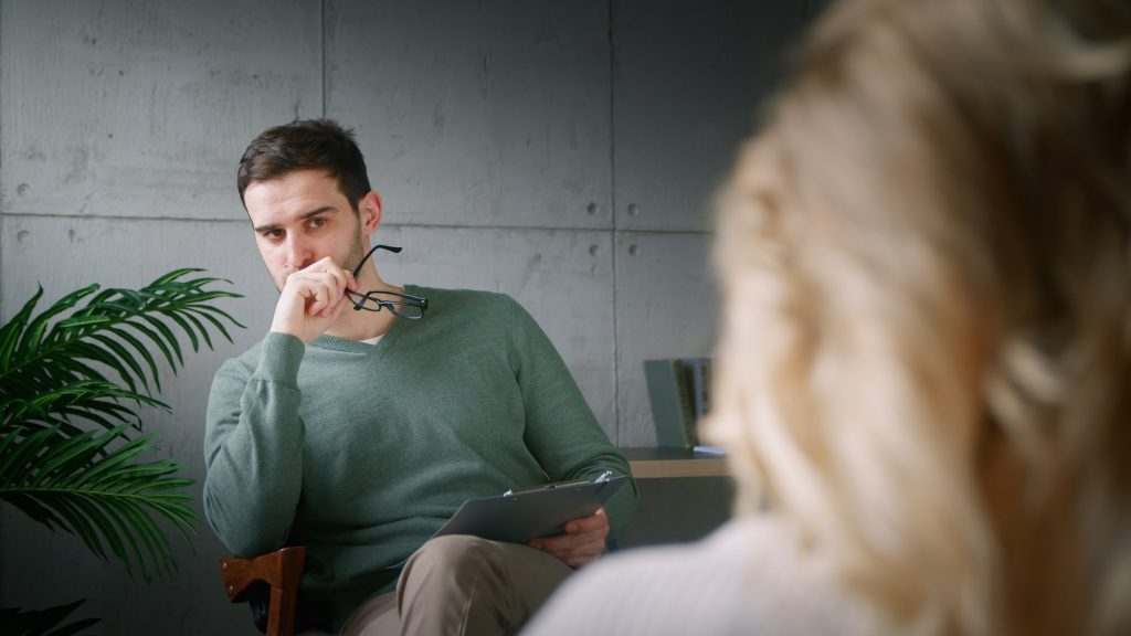 Young man with clipboard at psychotherapy in office