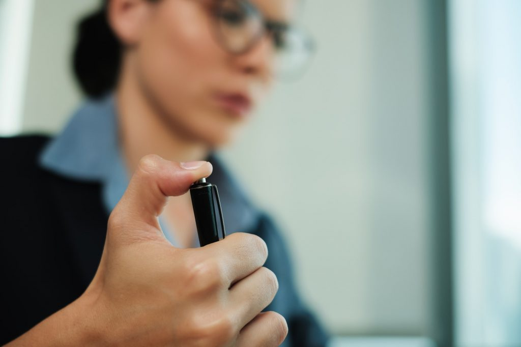 Bored Businesswoman Clicking Pen Repeatedly While Working at Office
