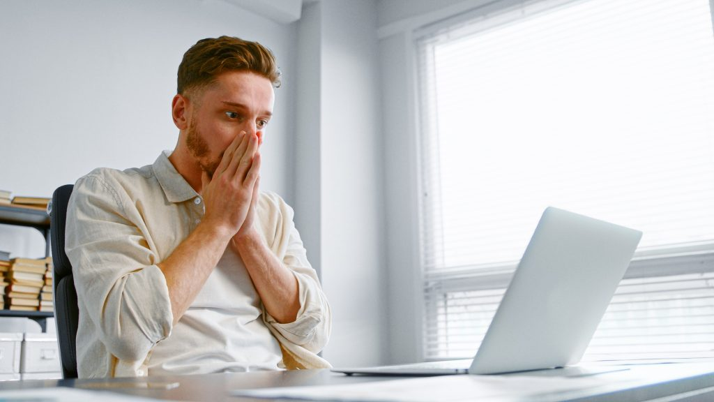 Depressed man looks at laptop with lost internet connection