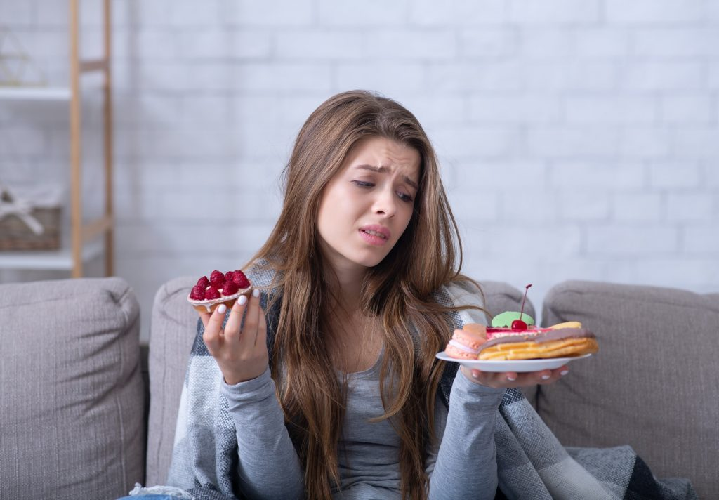 Depressed young lady having eating disorder, comforting herself with sweets on sofa at home