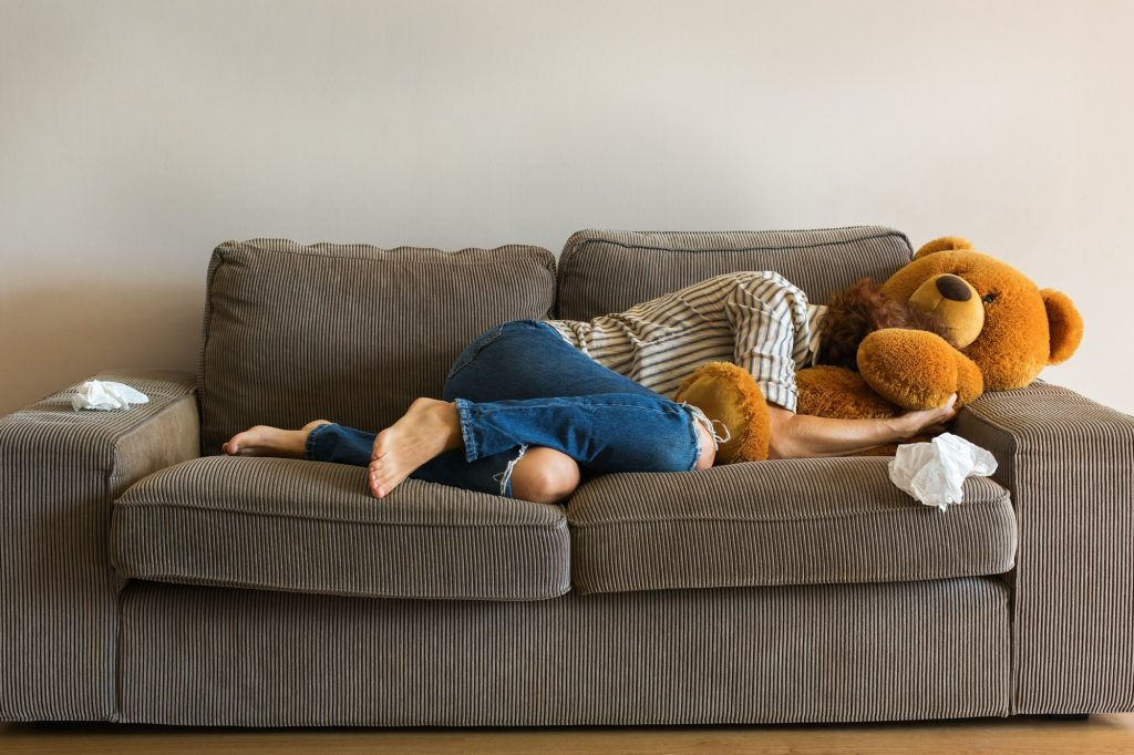Depressed young woman crying on the couch, stress, anxiety, loneliness