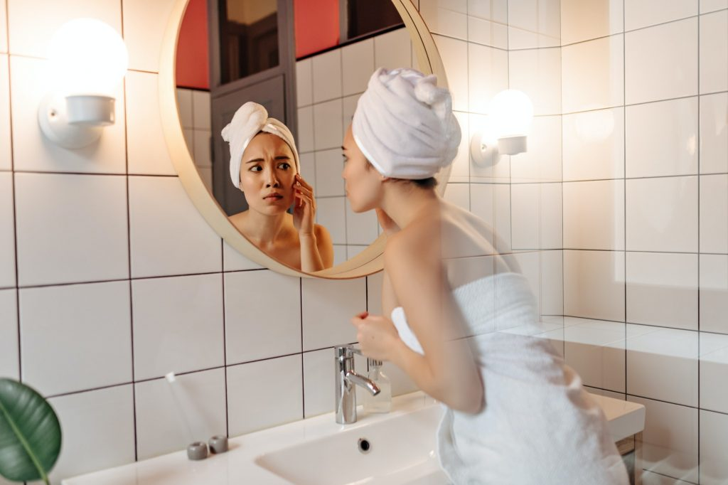 Woman in towel after shower anxiously looks in bathroom mirror