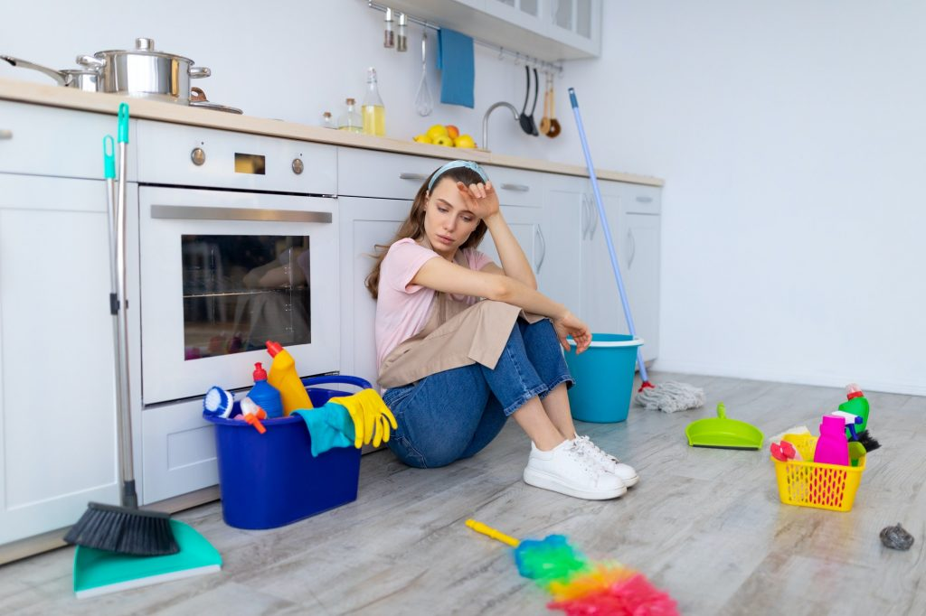 Depressed young housewife feeling tired from domestic chores, sitting on floor at kitchen