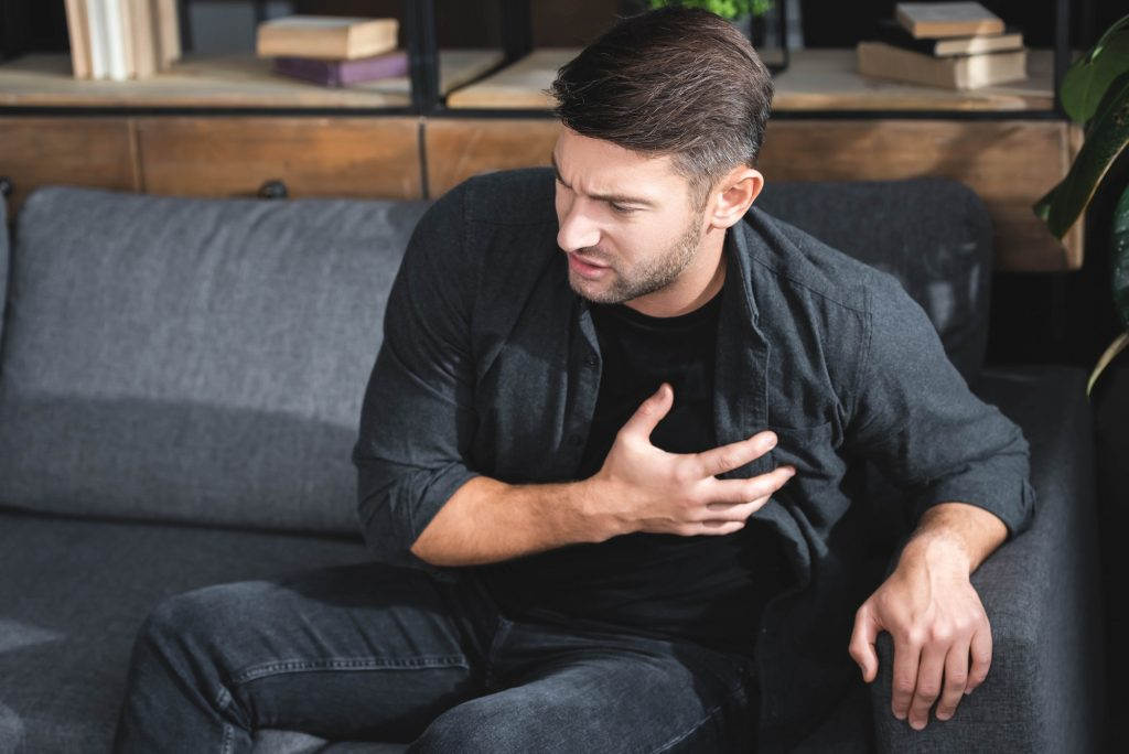 handsome man in shirt having heart attack in apartment