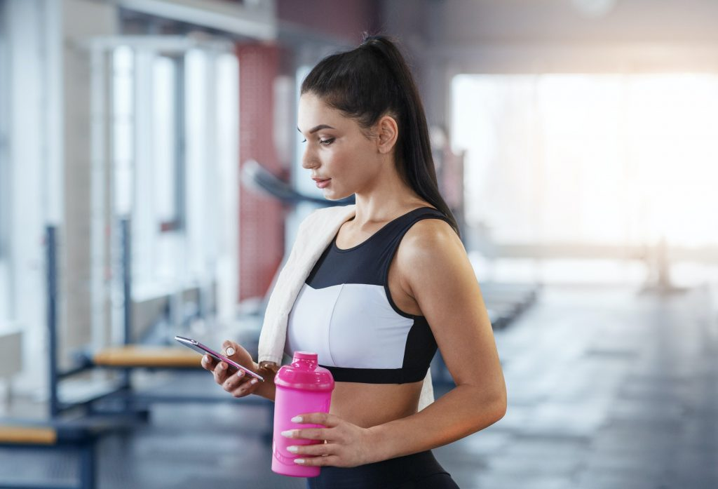 Millennial woman with mobile phone and bottle of water or protein shake at gym