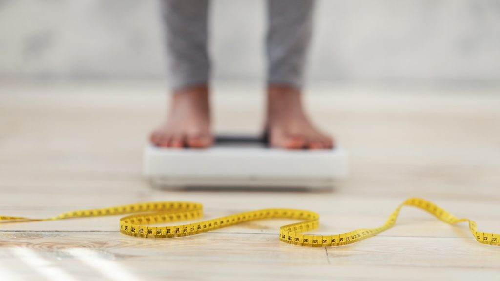 Unrecognizable black lady standing on scales, checking her weight, focus on measuring tape