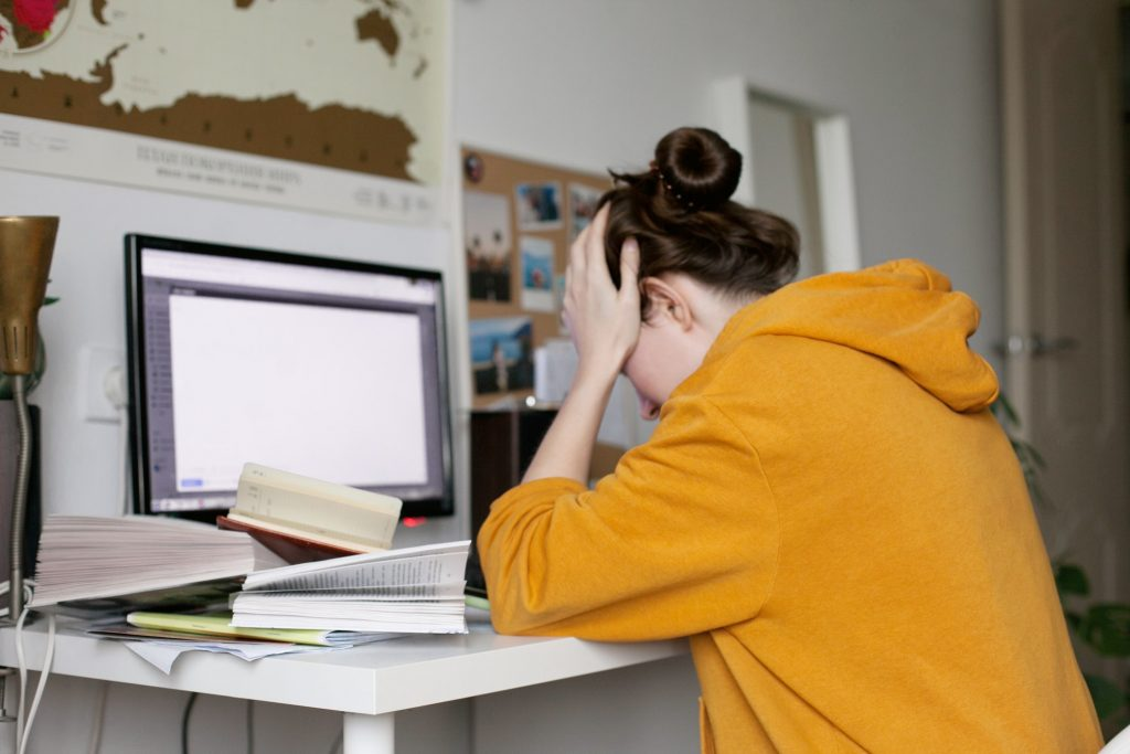 Woman in panic and stress about work sitting at messy desk suffering from emotional burnout
