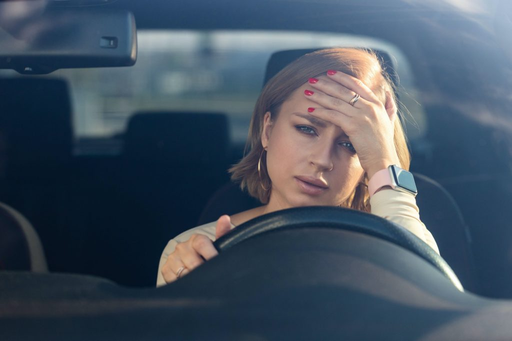 Exhausted woman driver sitting in car feeling emotional burnout after work looking at camera.