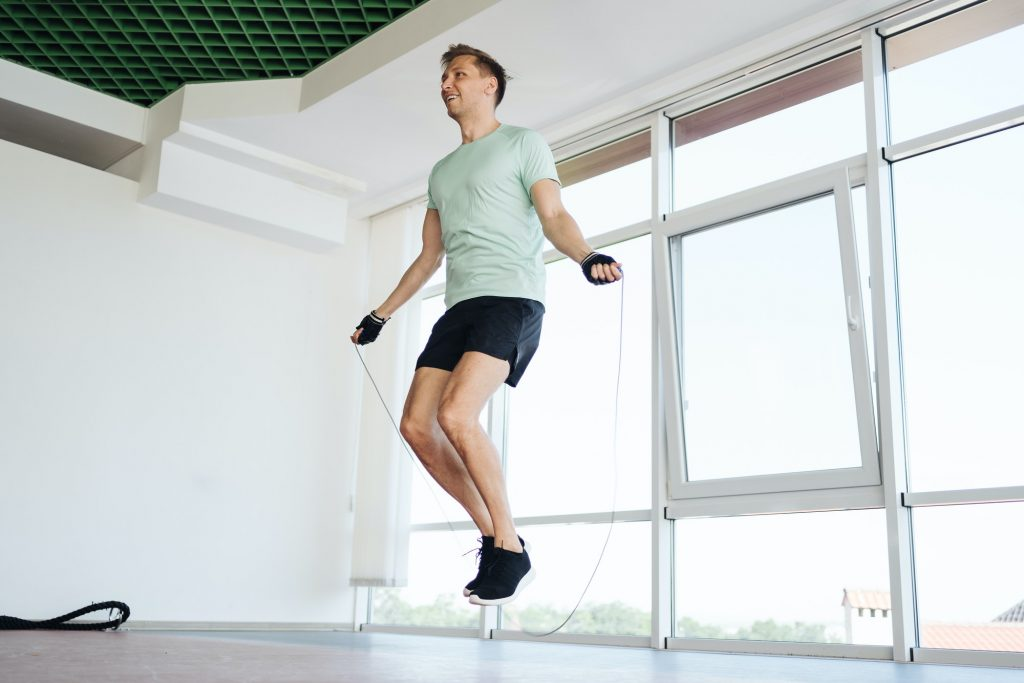 Handsome young man jumping over skipping rope working out