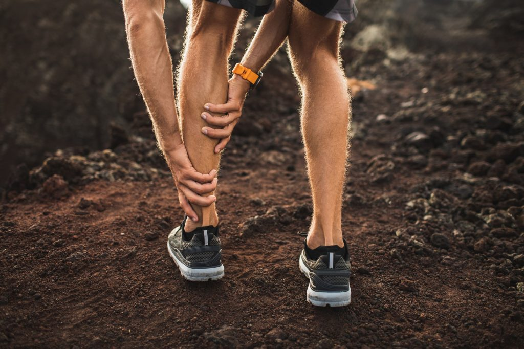 Male runner holding injured calf muscle and suffering with pain. Sprain ligament while running
